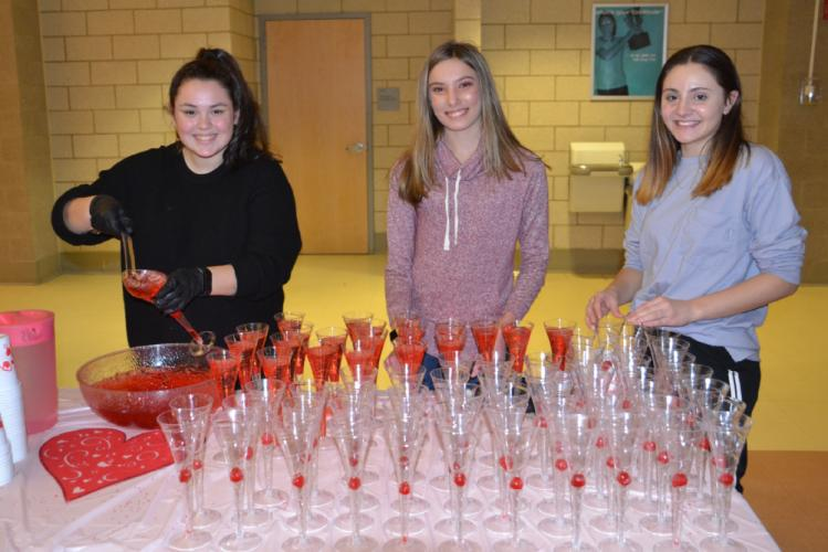 Pictured from left is high school junior Simone Paradis and middle school students Emily Litke and Erin Kornhaas of Girl Scout Troop 50371 who volunteered their time pouring drinks for guests at the Second Annual Daddy & Daughter Valentine Ball on…