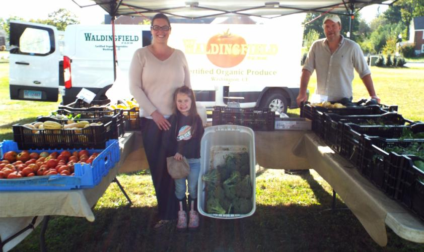 Amy and Sophia Tilford visited Waldingfeild Farm owner Quincy Horan at his tent at the Newtown Farmer's Market at Fairfield Hills on October 3. Both enjoyed the selection of produce the farm provided, like Russian kale. (Bee Photo, Silber)