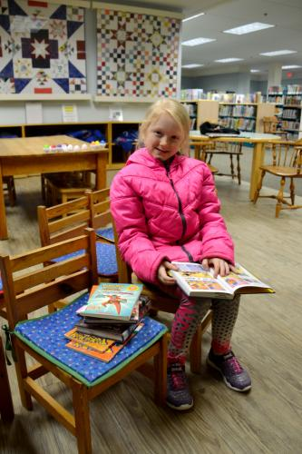 """In the C.H. Booth Library's Children's Department Evie Ekman, 8, reads """"Dog Man,"""" on January 29. (Bee Photo, Silber)"""