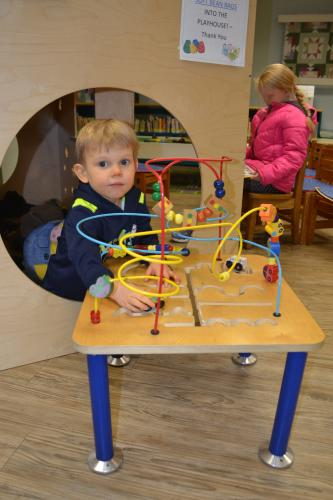 Three-year-old Jack Segarra plays with one of the toy tables in the C.H. Booth Library's Children's Department on January 29. (Bee Photo, Silber)