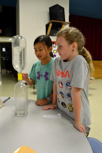 At the Science and Health Expo, Head O' Meadow fourth grader Grace Newsom points to the water flowing in the tornado simulator as fellow Terrifying Two Tornado Girls member Kiersten Daigle looks on. (Bee Photo, Silber)