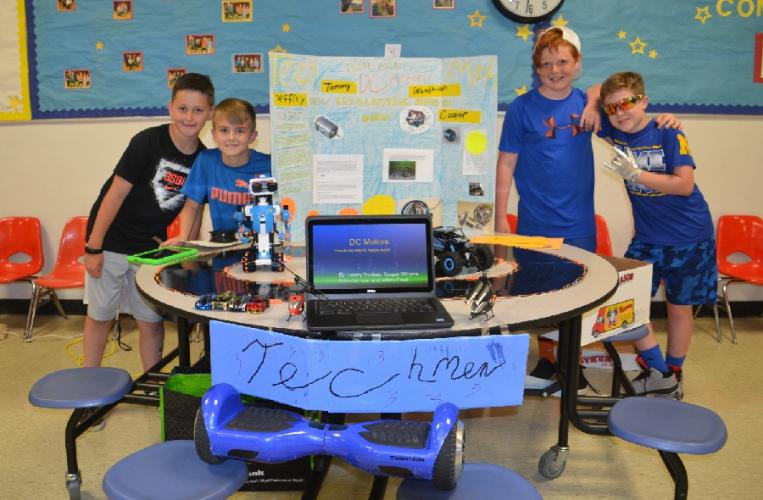 Members of Tech Men, from left, Cooper Williams, Jeffrey Prout, Sebastian Los, and Tommy Trudeau investigated how toy electric motors work and brought in examples for their Science and Health Expo display. (Bee Photo, Silber)