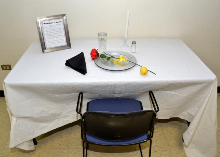 At Head O' Meadow Elementary School, a small table was set up with a white cloth, white candle, lemon, salt, glass, black napkin, red rose, ribbon, and an empty chair. Each item represented a different aspect of war and missing soldiers to serve as…