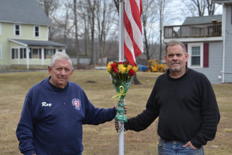 Ray Fuller, left, and his son Jeff, both of Hawleyville Volunteer Fire Company, secured a bouquet of flowers to the firehouse's flagpole, with its flag lowered to half-staff, on February 15. The Fullers were honoring the students and faculty members…