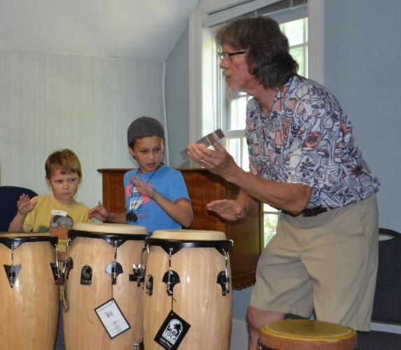 Music teacher Brad Peterson teaches brothers Andre, left, and Isaac St Georges drumming techniques on conga drums as he creates a rhythm for them to follow during the C.H. Booth Library's Multicultural Music class. (Bee Photo, Silber)