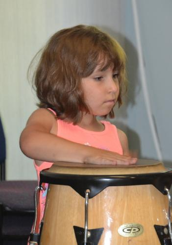 Barbara Andersen, 6, practices her drumming on the conga at the C.H. Booth Library's first Multicultural Music class on Monday, July 9. (Bee Photo, Silber)