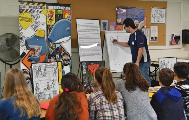 Cartoonist and comic book creator Matt Ryan of Free Lunch Comics showed students how to draw different elements in cartoons like character's facial features and gestures. (Bee Photo, Silber)