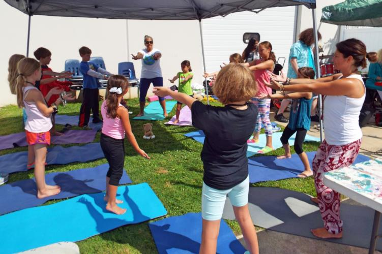 Outside on the NYA's courtyard, Youth Nation Yoga offered a variety of activities for children during the Newtown Yoga Festival. Youth Nation Yoga founder Denise Nobile, back center, and her assistant Shannon Carrizzo, left, led the group in…