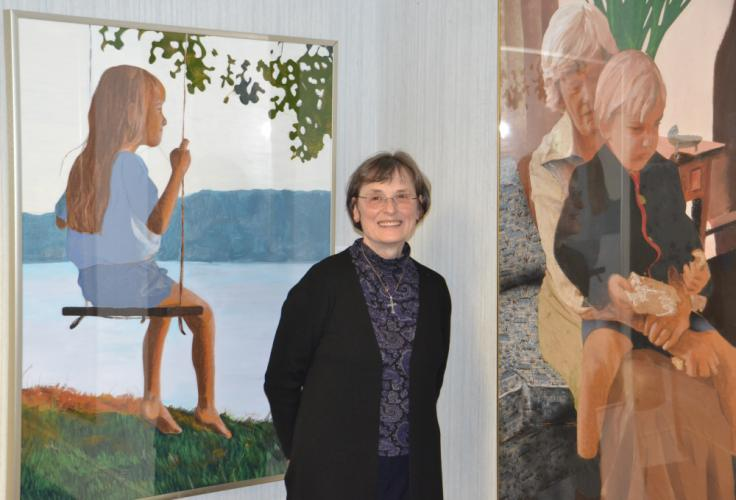 "Mixed media artist Carol Gaulin-McKenzie stands beside her artwork ""Girl on Swing,"" left, and ""Grandma,"" during the opening reception on February 4. Ms Gaulin-McKenzie is one of three artists featured in C.H. Booth Library's exhibition on display…"