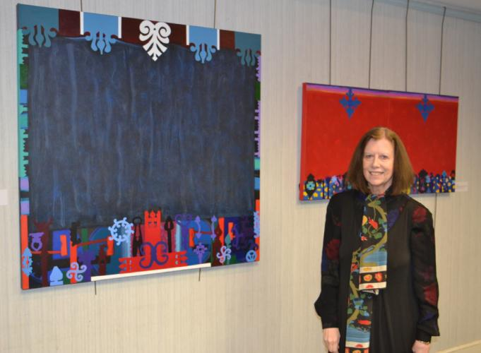 "Pictured is artist Stephanie Adam at the C.H. Booth Library's opening reception with two of her acrylic paintings. On the left is her canvas painting titled ""Wooden Hangers,"" and behind her is ""Door Knockers on Floor Grates."" (Bee Photo, Silber)"