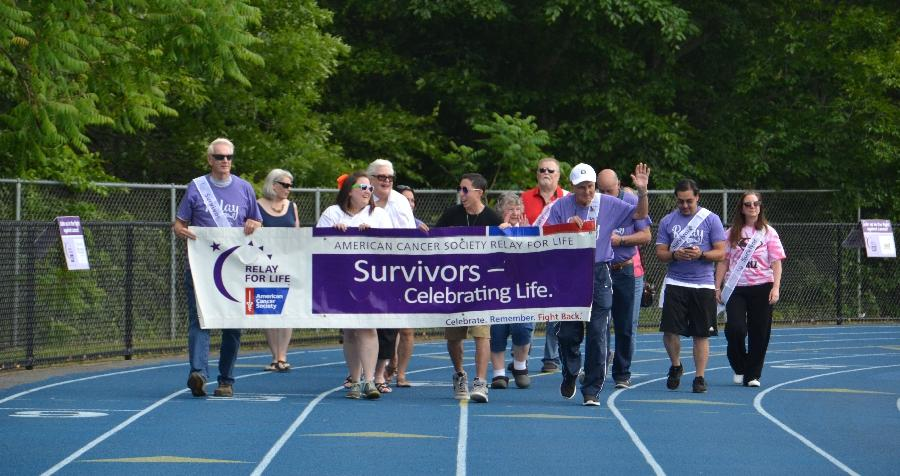 Local cancer survivors walk the first official lap of the night around the Newtown High School track at Relay For Life on Saturday, June 16. (Bee Photo, Silber)