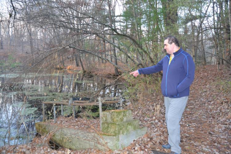 Sandy Hook Permanent Memorial Commission member Dan Krauss has volunteered his time conducting guided site walks of the memorial property for potential designers. Here he shows the old diving board that dips into one of the ponds. (Bee Photo, Silber)