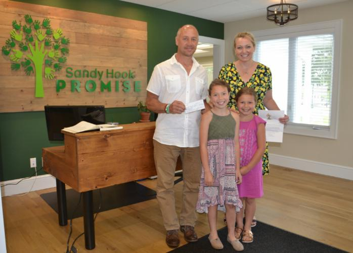 Sandy Hook Promise Founders and Managing Directors Mark Barden and Nicole Hockley met with Grace, left, and Abigail DellaVentura of Roots4Relief, who donated $1,500 to Sandy Hook Promise on July 5.  (Bee Photo, Silber)