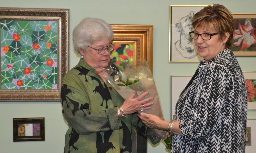 Newtown Senior Center Director Marilyn Place, pictured right, presents Jaynis Pixley with a bouquet of flowers at the end of Ms Pixley's gallery presentation on May 22. (Bee Photo, Silber)