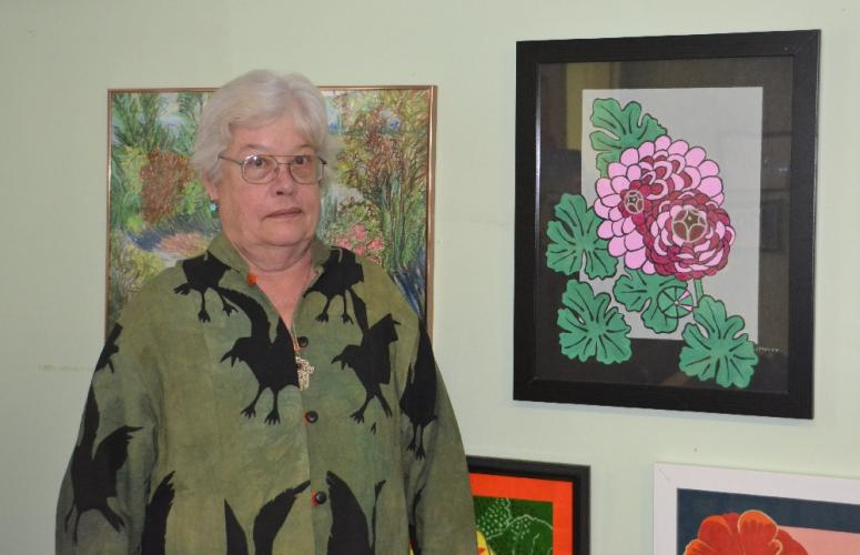 Newtown resident Jaynis Pixley stands beside one of her favorite paintings of a purple ranunculus flower that is featured in her collection of artwork on display at the Newtown Senior Center, 14 Riverside Road, until mid-June. (Bee Photo, Silber)