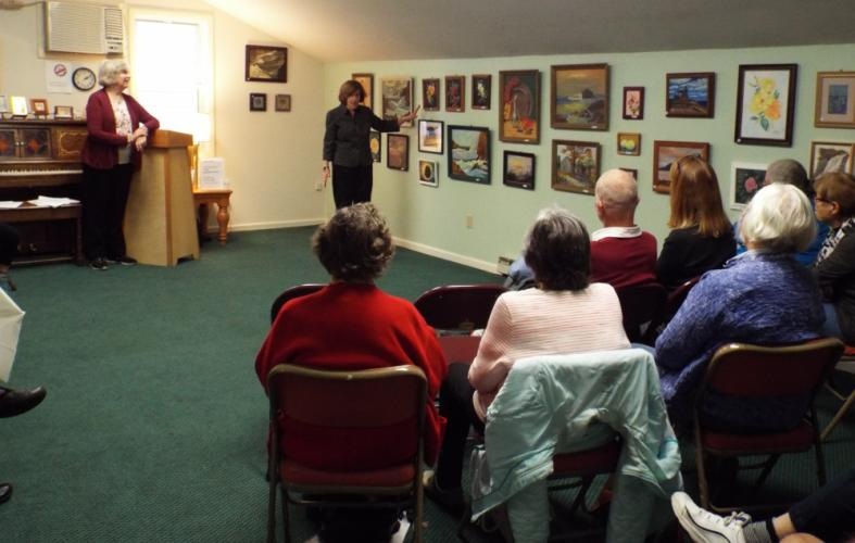 """Both Mary Goebel, at podium, and Joyce Goldin had the opportunity to speak about their journey as an artists, discuss specific pieces on display, and answer audience questions during the opening reception for their art exhibit """"Every Picture Has A…"""