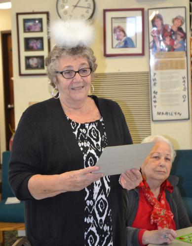 During the Newtown Senior Center's Holiday Bingo, Karin Aurelia helped read off the numbers on Luella Dwyer's winning card. (Bee Photo, Silber)