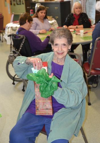 At the Senior Center's Holiday Bingo on December 20, Mary Ann Posser won a variety of prizes, including a notepad. (Bee Photo, Silber)