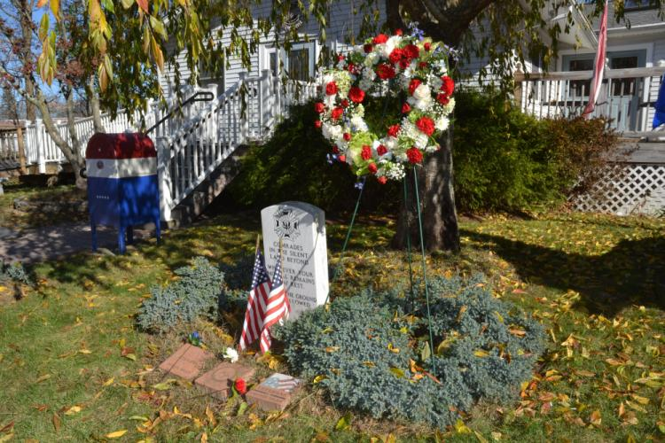 During the Veterans Day Ceremony on November 11, a commemorative wreath, as well as red, white, and blue carnations were placed by the veterans' memorial stone outside the VFW. (Bee Photo, Silber)