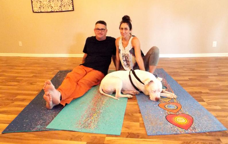 The Yoga Mat Art Show will take place at The Newtown Yoga Center, 78 South Main Street, Friday, October 6. Pictured is local artist Dave Brooker and Newtown Yoga Center owner Aline Marie, who have created all the hand painted yoga mats for the event…