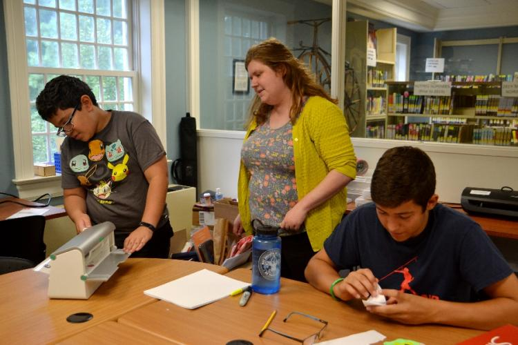 Pictured from left is Jonathan Ramzy using the C.H. Booth Library's new adhesive machine for making stickers, during the chbMAKER'S Corner craft session on August 8. Young Adult Librarian Abbey Lynch supervises, and John Boccuzzi works on his next…