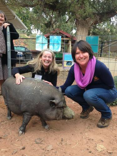 Harmony Verna of The Animal Center, left, and Jenny Hubbard, a founder of The Catherine Violet Hubbard Foundation, visit with a pot bellied pig during a recent visit to Best Friends Animal Sanctuary in Utah. The women took part in classes on…