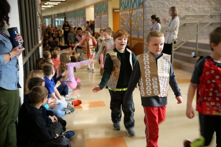 Sandy Hook School first graders Rulon Snellman and Shea Platt, front right, walk as part of the parade for the 100th day of school on February 5. All of the first graders wore vests decorated with 100 items for the occasion. (Bee Photo, Hallabeck)