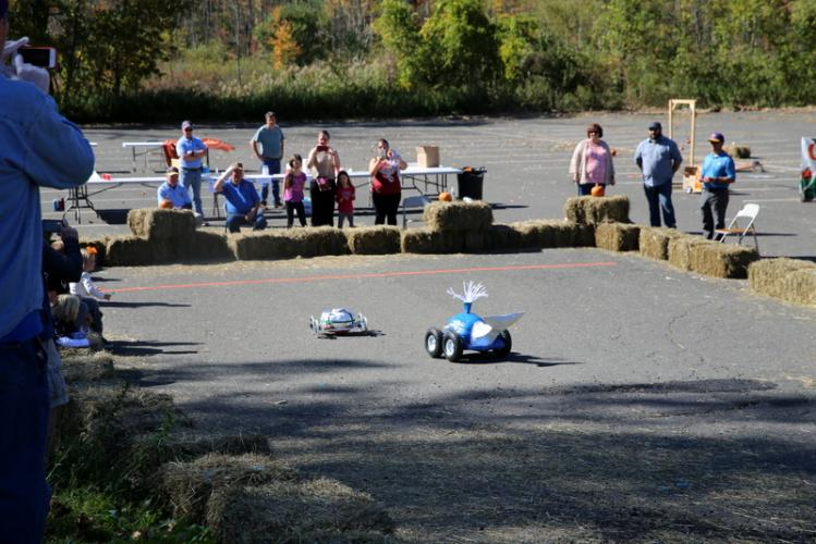 Siblings Ivy and Noah Masotta's pumpkin racer, left, led the way in the final race of the 2017 Great Pumpkin Race at Edmond Town Hall, with Angelo DiCicco's close behind. (Bee Photo, Hallabeck)