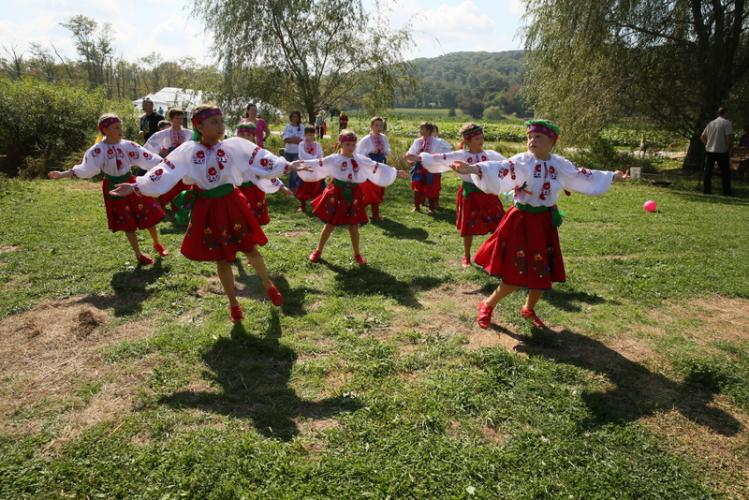 Members of the Kalynonka dance group of Stamford rehearse before performing for a crowd under a pavilion at Paproski's Castle Hill Farm on September 17. (Bee Photo, Hallabeck)