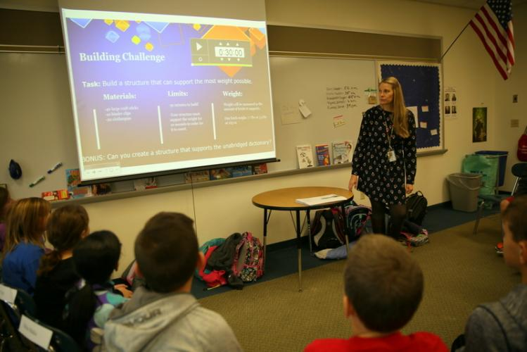 Project Challenge teacher Kate Magness presents a building challenge to fourth grade students at a class in late November. The students were challenged to use craft sticks, binder clips, and clothespins to build a structure that could support weight…