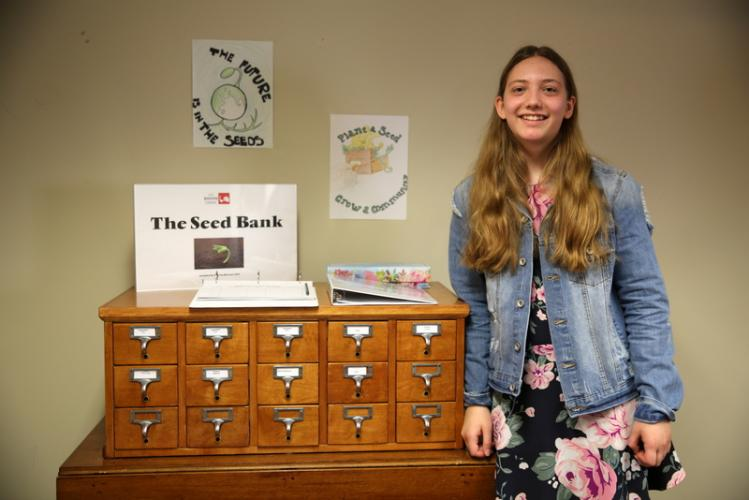 Sabrina Boccuzzi stands next to the Seed Bank she created for C.H. Booth Library, during the grand opening event on May 5. (Bee Photo, Hallabeck)