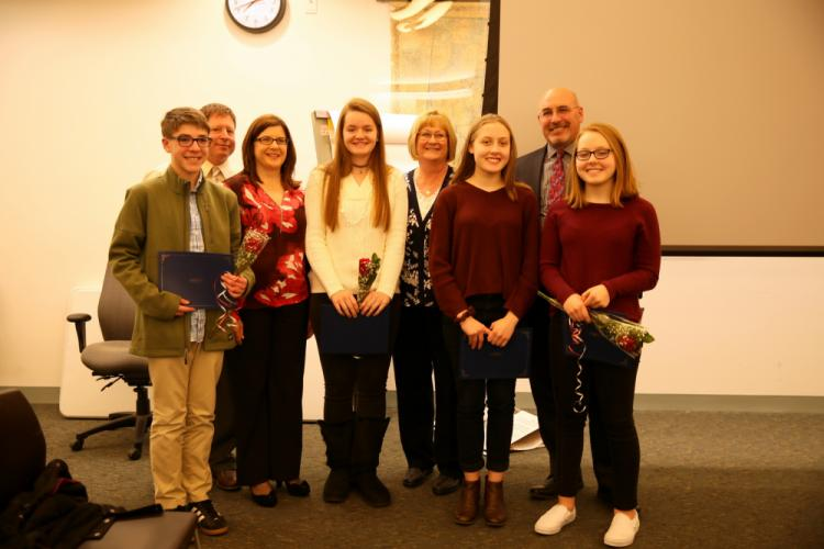 From left, eighth grader Kyle Trahan, NMS Assistant Principal James Ross, NMS teacher Karen Colwell, ninth grader Virginia Hepp, NMS teacher Abigail Olsen, ninth grader Aliya Hafiz, NMS Principal Thomas Einhorn, and ninth grader Sofiya Hafiz stood…
