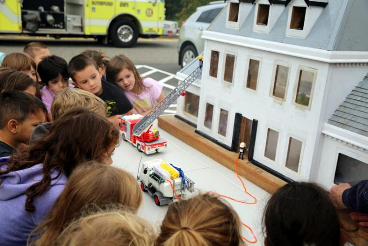 Middle Gate Elementary School students huddle around a dollhouse to watch a demonstration of how firefighters, shown as Lego characters, respond when a house is on fire. (Bee Photo, Hallabeck)