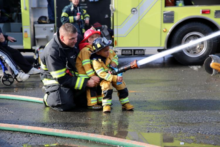 Botsford Fire Rescue Lieutenant Tommy Paloian, left, oversees Brody Taylor, right, and Dominic Giordano spraying water at the November 4 open house event. (Bee Photo, Hallabeck)