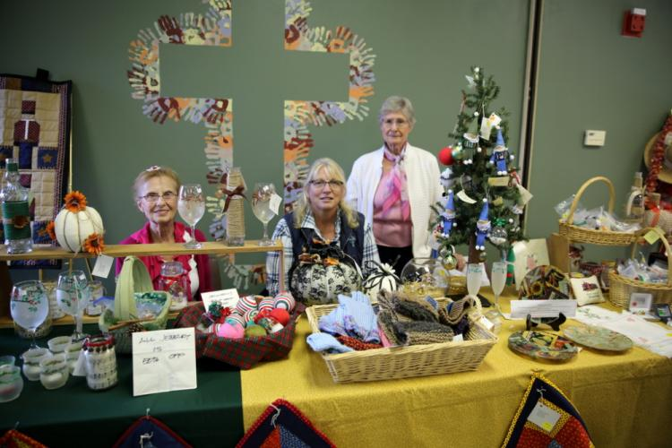 From left, Jo Anderson, Lori Falndreau, and Dorothy Lange oversee a church craft table at the Christ the King Lutheran Church Fall Fair. (Bee Photo, Hallabeck)
