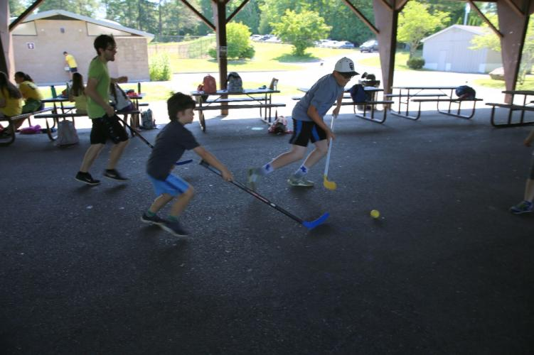 Dickinson Memorial Park Day Camp staff member Jonah Santiana plays hockey with campers Spencer Hull, center, and Jack Cartolano on July 12 under the park's pavilion.   (Bee Photo, Hallabeck)