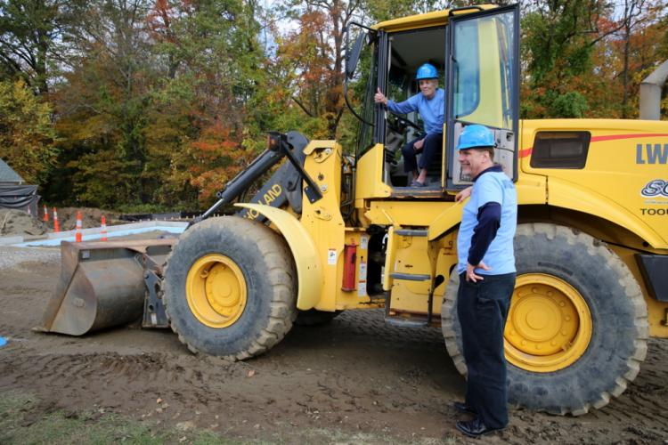 Peter Cloudas, FAITH owner's representative for the building project, stands next to an excavator, while FAITH Food Pantry President Lee Paulsen tries out the front seat for size.  (Bee Photo, Hallabeck)