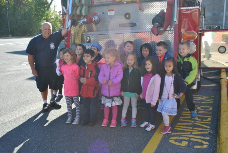 Newtown Hook & Ladder Firefighter Tim Gies stands with Hawley Elementary School kindergarten students on Tuesday, October 11, after a presentation.  (Bee Photo, Hallabeck)