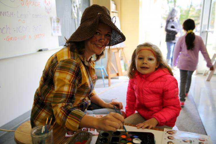 Fraser Woods Montessori School teacher Cynthia Wilson paints 4-year-old Riley Smith's face at the November 4 Fall Family Festival. (Bee Photo, Hallabeck)