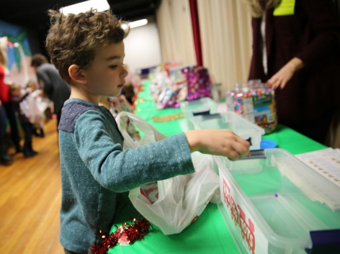Head O' Meadow kindergartener Mason Tietjen drops a bead into a bin to vote for his $1 to be donated to the US Marine Corps Reserve Toys For Tots program. (Bee Photo, Hallabeck)