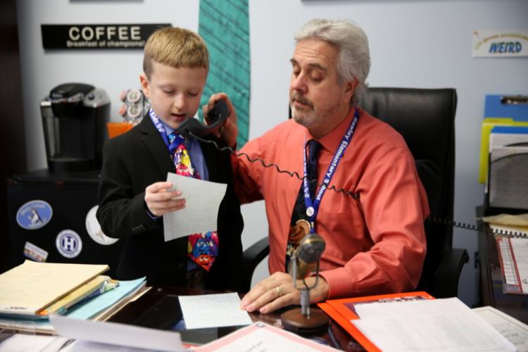 Hawley second grader and Principal of the Day Alex Gadbut shares a decree during the morning announcement on November 20, with the help of Principal Christopher Moretti, that all students can have an extra recess for the day. (Bee Photo, Hallabeck)