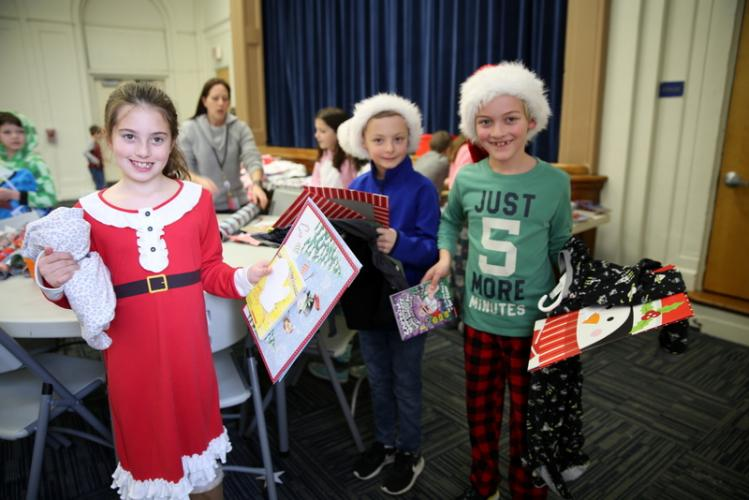 From left, Delaney Albert, Evan DePasquale, and Finn Clancy pose with the gifts and wrapping paper they chose on December 13. (Bee Photo, Hallabeck)