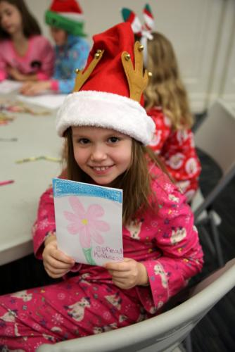Hawley third grader Keira Hintze holds up a card she drew that will go with a gift to the Women's Center of Greater Danbury. (Bee Photo, Hallabeck)