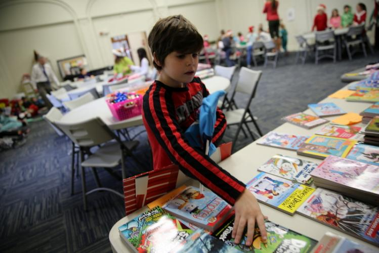 Third grader Mason Symes picks a book to wrap with a pair of pajamas that will be donated to the Women's Center of Greater Danbury. (Bee Photo, Hallabeck)