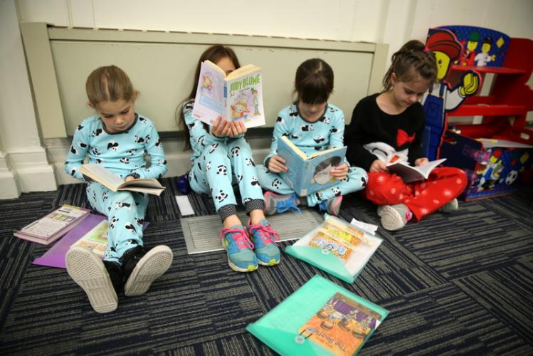 Hawley third graders, from left, Piper Feli, Ana Morris, Logan LeRow, and June Cash read between wrapping presents and making cards. (Bee Photo, Hallabeck)