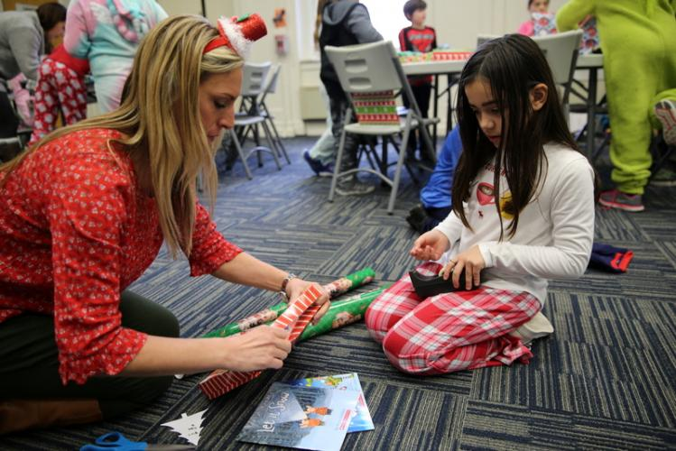 Hawley third grade teacher Tracy Galassi helps student Anna Pinto wrap a present that will be given to the Women's Center of Greater Danbury.  (Bee Photo, Hallabeck)