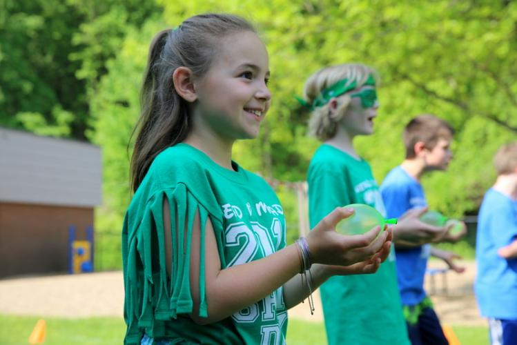 Head O' Meadow Elementary School third grader Claire Caico holds a water balloon before throwing it to a partner in a water balloon toss station during the school's Spirit Day on May 24. The entire day had a sportsmanship theme. (Bee Photo, Hallabeck)