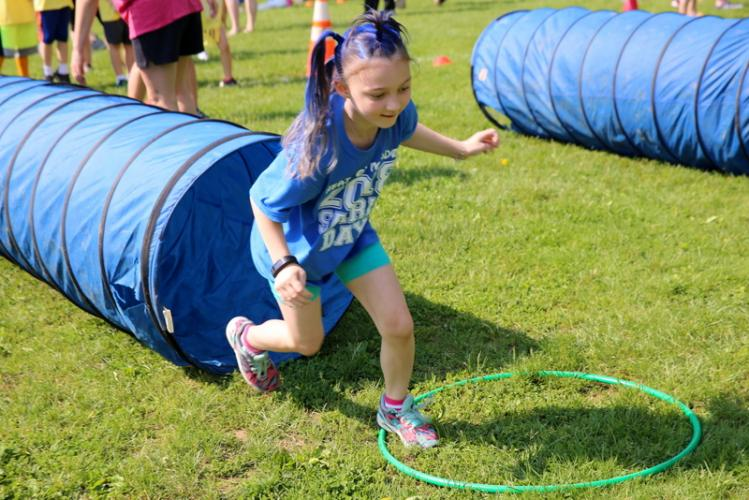 Head O' Meadow Elementary School student Peightyn Skerencak makes her way out of a tube to jump between hula hoops at one station at the school's May 24 Spirit Day. (Bee Photo, Hallabeck)