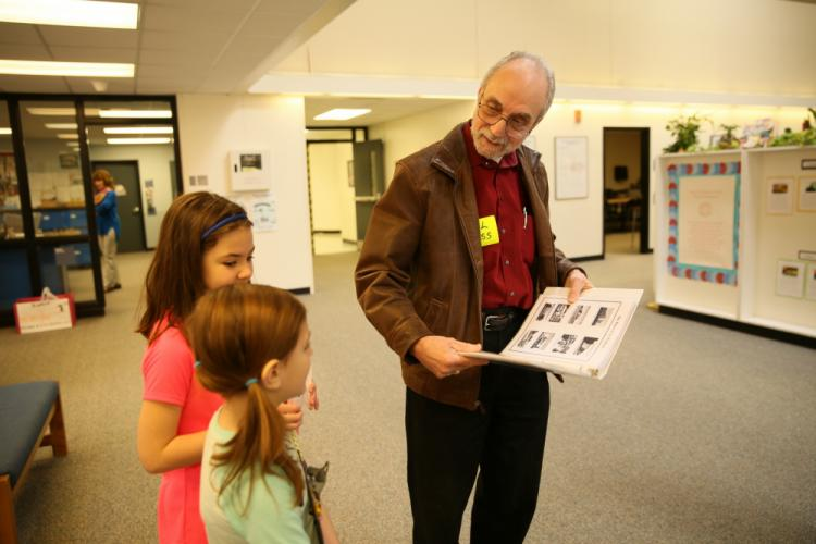 Phil Gross met Head O' Meadow fourth grader Caroline Murray, back, and second grader Eileen Celli, before the pair teamed up to ask him questions about his life. Mr Gross came prepared with a book he wrote about his life to share with the students. …