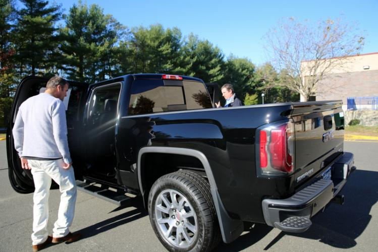 Fairfield resident Mark Ford, left, looks at a 2017 Sierra Denali truck at NHS on October 21 with Ingersoll Auto of Danbury representative Brian Kurth, far right. Mr Ford was one of 180 people to test drive a vehicle to raise money for the NHS…